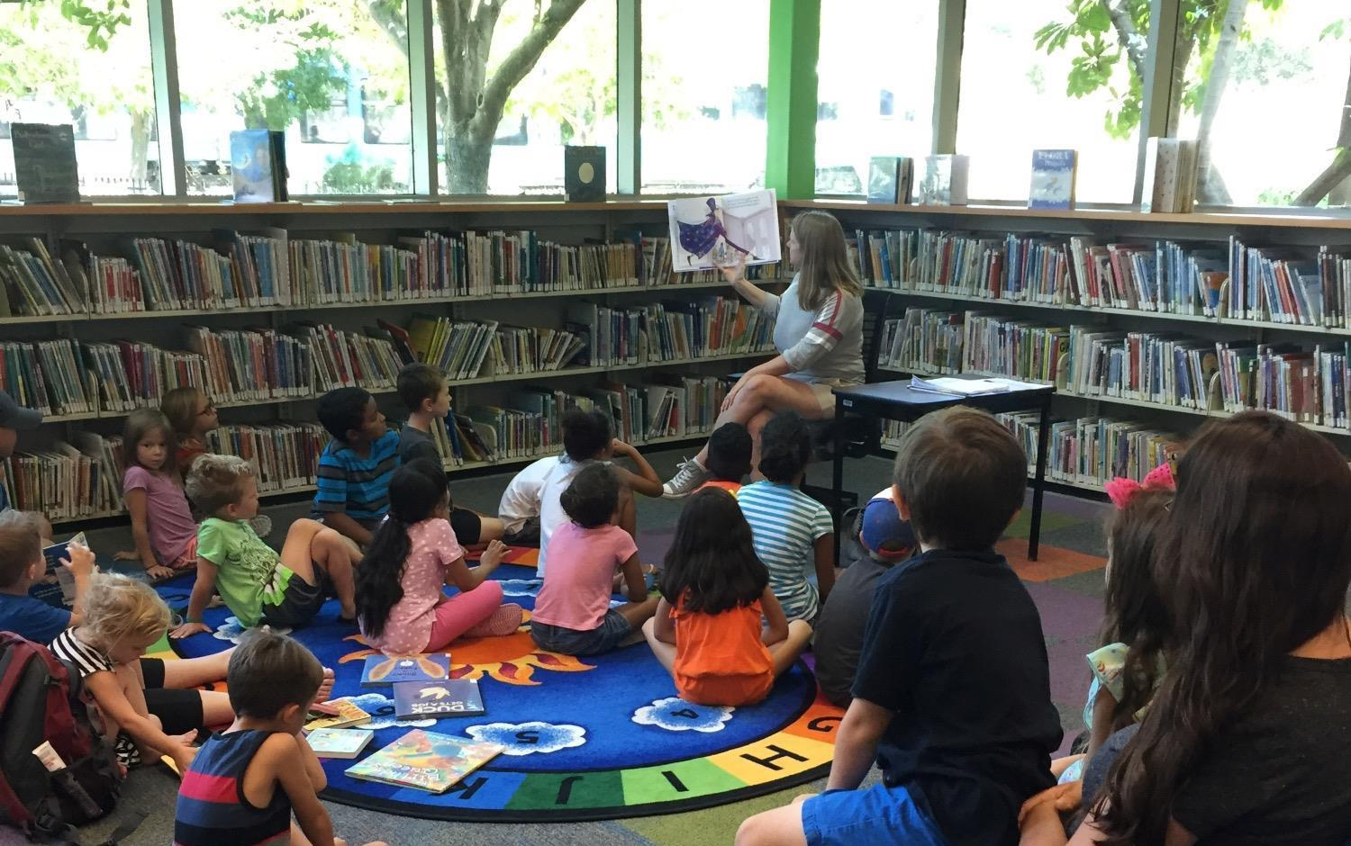 Teacher reading to kids at library